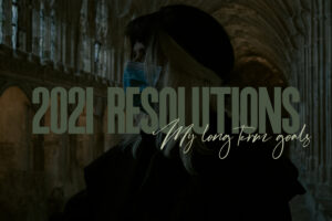 featured image for 2021 resolutions. image shows a girl wearing a mask stood in the cloisters of Gloucester Cathedral