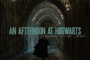 """featured image for post. image depicts a girl in a long black coat walking through a cathedral with the words """"an afternoon at hogwarts"""""""